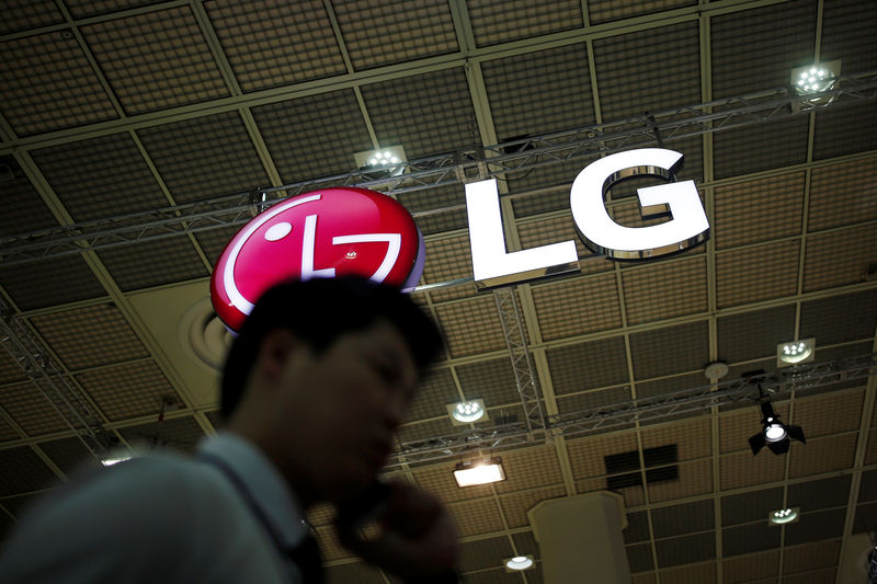 © Reuters. A man talking on his phone walks past the logo of LG Electronics during Korea Electronics Show 2016 in Seoul