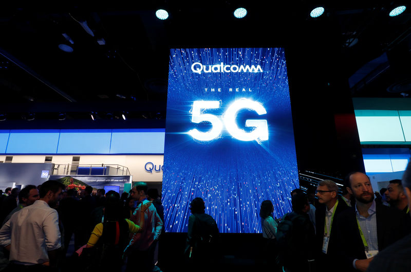 © Reuters. People pass a video display promoting 5G connectivity at the Qualcomm stand during CES 2019 in Las Vegas