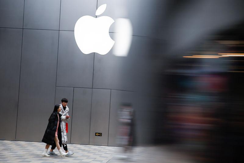© Reuters. Прохожие у магазина Apple в Пекине