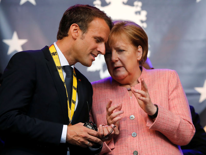 © Reuters. FILE PHOTO: French President Emmanuel Macron speaks with German Chancellor Angela Merkel after being awarded the Charlemagne Prize for
