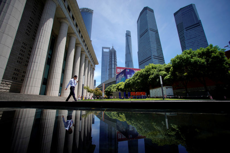 © Reuters. FILE PHOTO: A man walks at the Lujiazui financial district of Pudong in Shanghai
