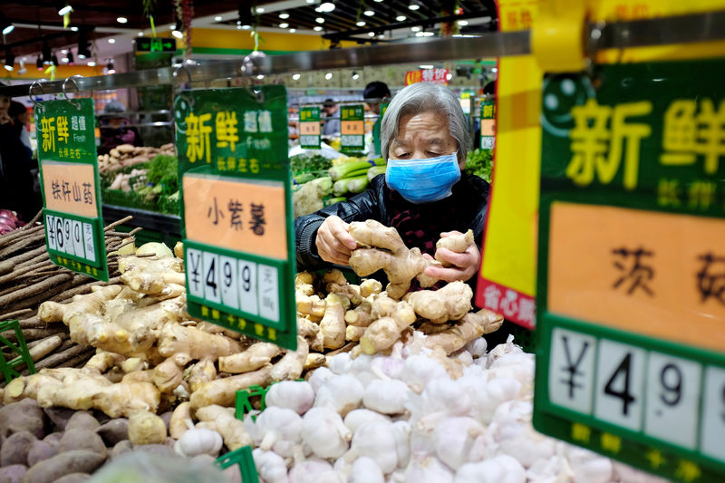 © Reuters. FILE PHOTO - A resident selects ginger at a supermarket in Beijing