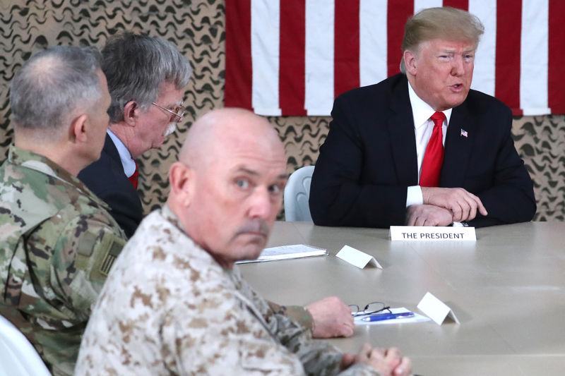 © Reuters. U.S. President Trump, flanked by National Security Adviser Bolton, meets political and military leaders during an unannounced visit to Al Asad Air Base, Iraq