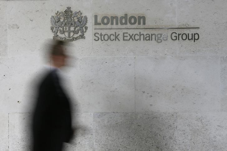 © Reuters. FILE PHOTO: A man walks past the London Stock Exchange in the City of London