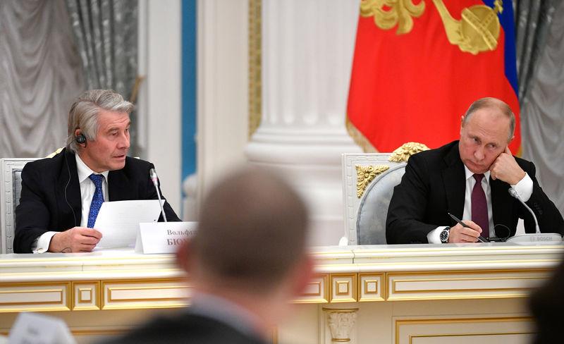 © Reuters. Президент России Владимир Путин и председатель немецкого Комитета по восточноевропейским экономическим отношениям Вольфганг Бюхеле на встрече с немецкими предпринимателями в Кремле