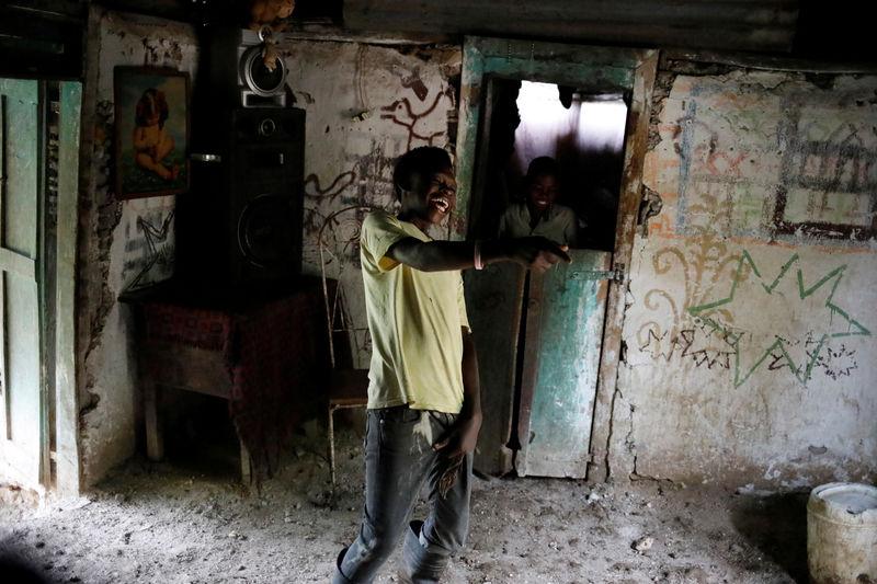 © Reuters. THE WIDER IMAGE: Un niño ríe mientras pasa el tiempo con amigos en una casa en Boucan Ferdinand, Haití