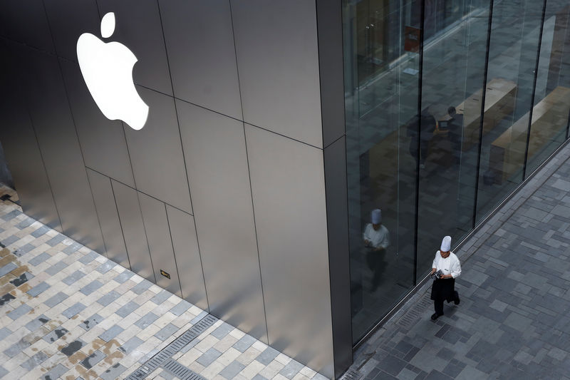 © Reuters. FILE PHOTO:  Chef walks past an Apple store in Beijing
