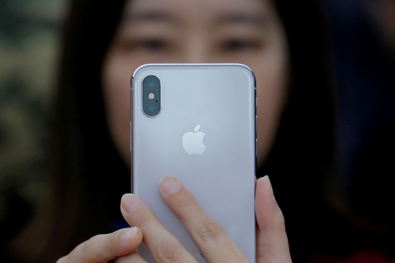 © Reuters. FILE PHOTO: An attendee uses a new iPhone X during a presentation for the media in Beijing