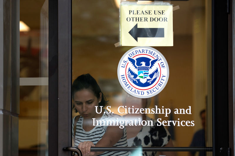 © Reuters. FILE PHOTO: A woman leaves the U.S. Citizenship and Immigration Services offices in New York
