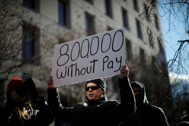 © Reuters. FILE PHOTO: Demonstrator holds a sign protesting the partial U.S. government shutdown