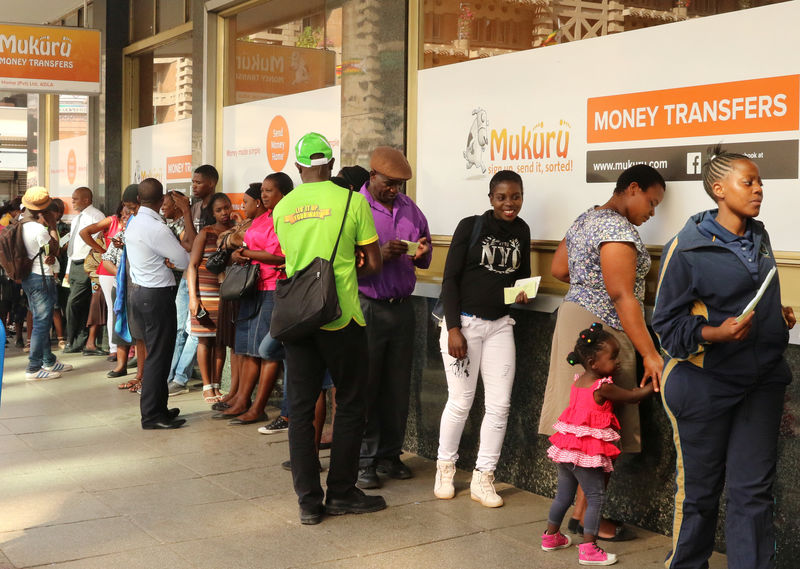 © Reuters. People queue to withdraw US dollars from a money transfer shop in Harare