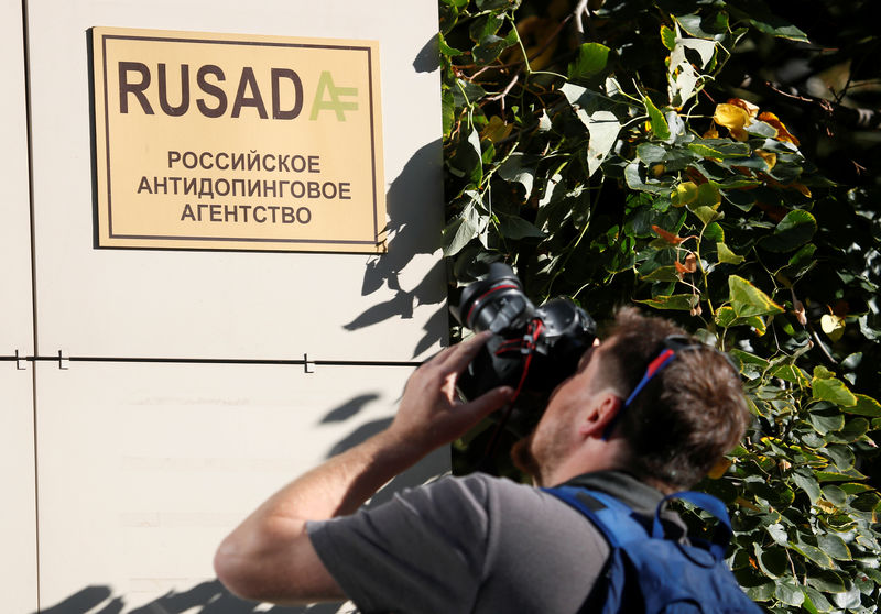 © Reuters. A photographer takes pictures of a sign outside the office of Russian Anti-Doping Agency in Moscow