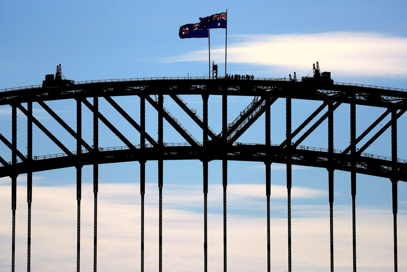 © Reuters. Tourists stand atop of the Sydney Harbour Bridge next to flag poles flying the New South Wales state and Australian national flags in Sydney