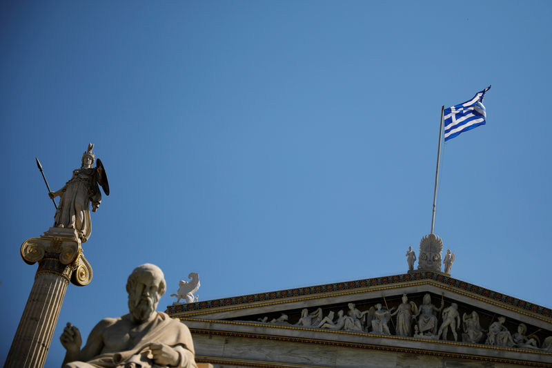 © Reuters. A Greek national flag flies atop the Athens Academy next to the statues of ancient goddess Athena and Greek philosopher Plato in Athens