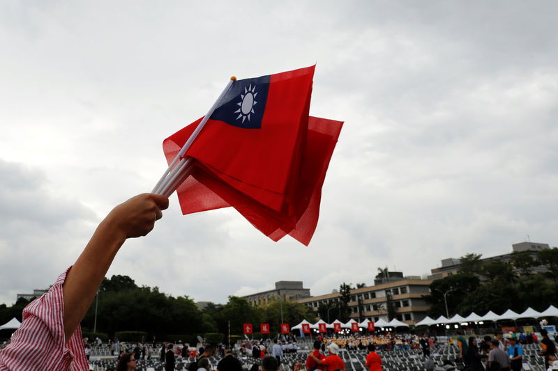 © Reuters. An audience waves Taiwanese flags during the National Day celebrations in Taipei