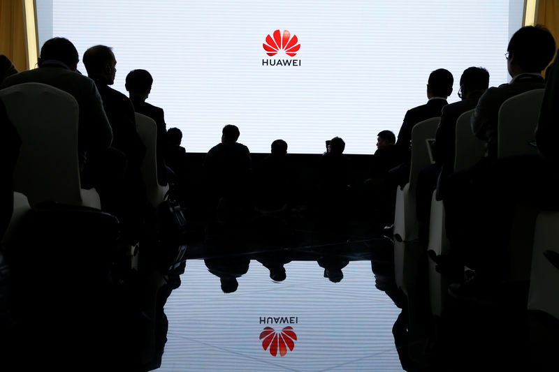 © Reuters. FILE PHOTO - People attend a product presentation at Huawei in Beijing