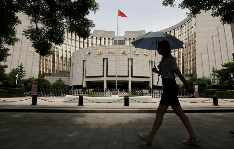 © Reuters. FILE PHOTO: Woman walks past the headquarters of the PBOC in Beijing