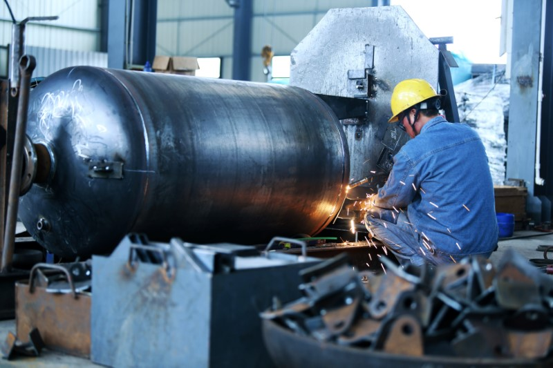 © Reuters. Worker welds pressure vessel into Nantong industrial equipment manufacturing company