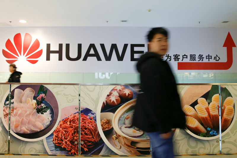 © Reuters. A man walks past a Huawei sign in a mall in Beijing