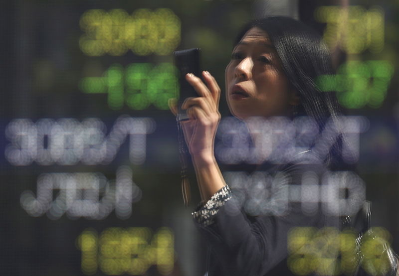 © Reuters. FILE PHOTO - A woman using a smartphone is reflected on a stock exchange outside brokerage in Tokyo, Japan