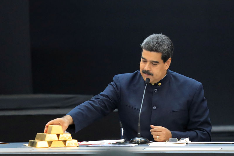 © Reuters. FILE PHOTO: Venezuela's President Nicolas Maduro touches a gold bar as he speaks during a meeting with the ministers responsible for the economic sector at Miraflores Palace in Caraca