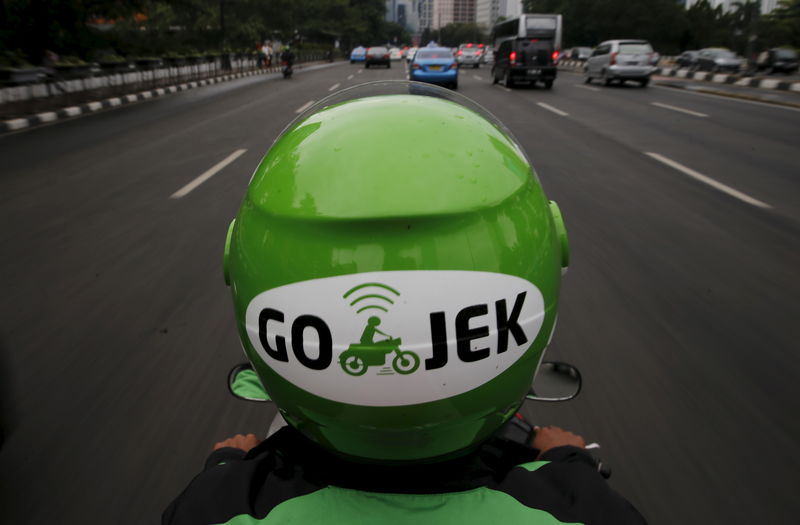 © Reuters. A Gojek driver rides his motorcycle through a business district street in Jakarta