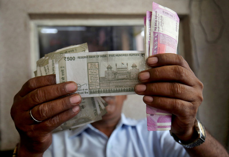 © Reuters. FILE PHOTO: A cashier checks Indian rupee notes inside a room at a fuel station in Ahmedabad