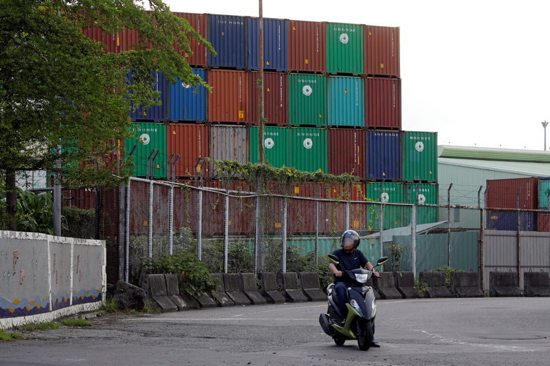 © Reuters. FILE PHOTO:  A man rides a motorbike near Kaohsiung Port