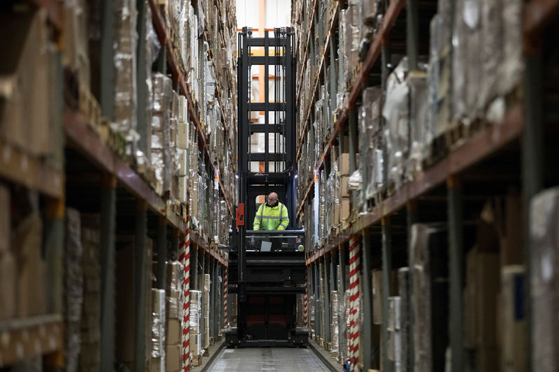 © Reuters. FILE PHOTO: An employee operates a forklift to move goods at the Miniclipper Logistics warehouse in Leighton Buzzard