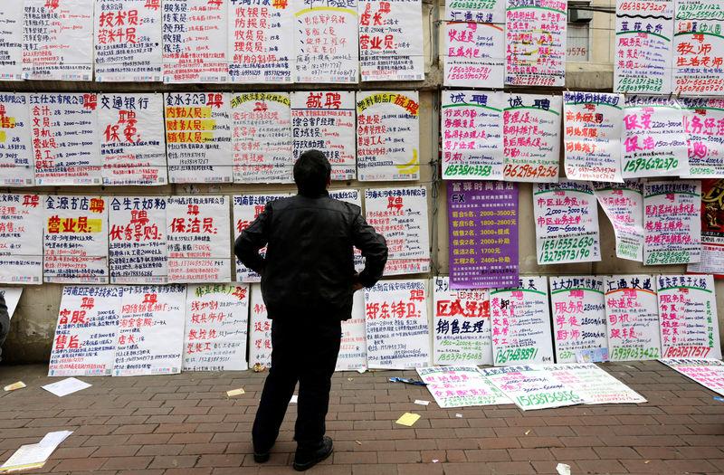 © Reuters. A man looks at job information at an employment fair beside a street in Zhengzhou