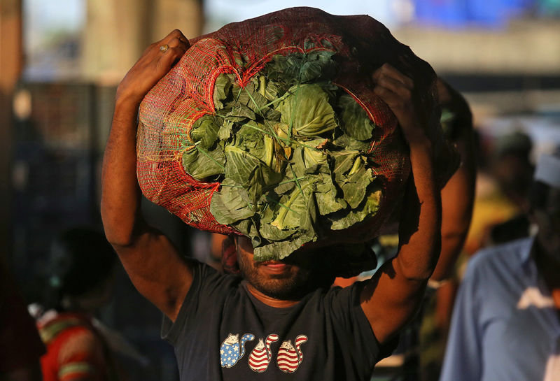 © Reuters. A man carries a sack filled with cabbage at a wholesale market in Mumbai