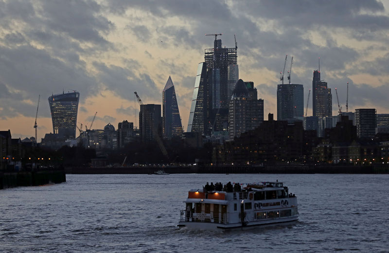 © Reuters. FILE PHOTO: A river boat cruises down the River Thames as the sun sets behind the Canary Wharf financial district of London