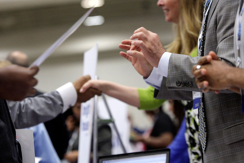 © Reuters. Corporate recruiters gesture and shake hands as they talk with job seekers at a Hire Our Heroes job fair targeting unemployed military veterans and sponsored by the Cable Show, a cable television industry trade show in Washington