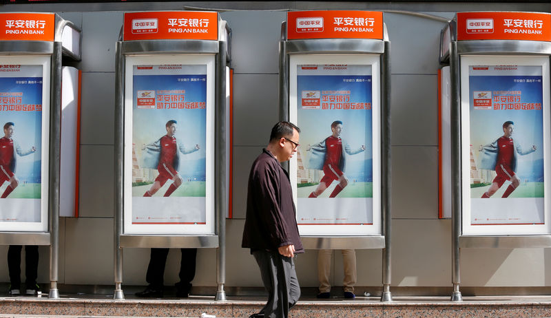 © Reuters. FILE PHOTO: A man walks past ATM booths of Ping An Bank in Shenzhen