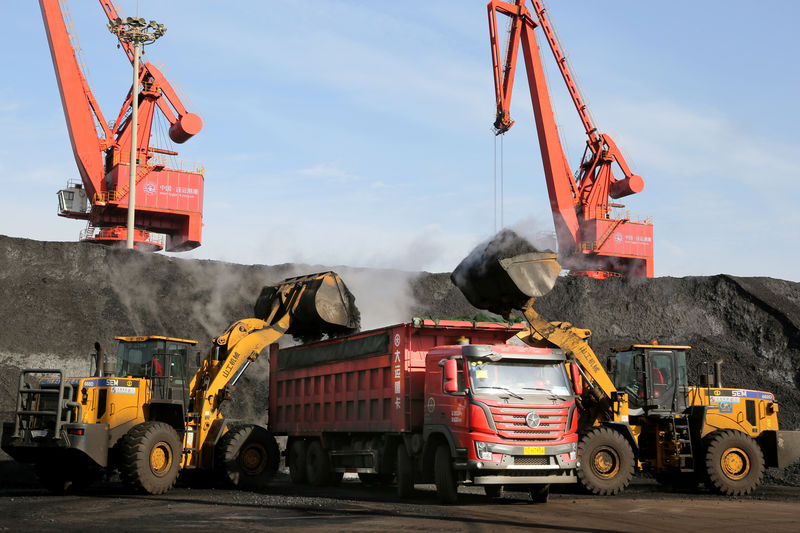 © Reuters. FILE PHOTO: Front loaders transport coal to a truck at a port in Lianyungang