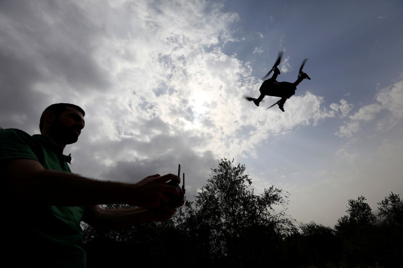 © Reuters. A man operates a drone over olive trees in Nabatieh