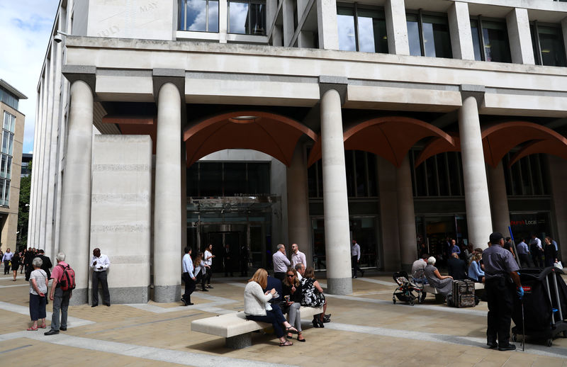 © Reuters. People stand and sit outside the London Stock Exchange in Paternoster Square, London