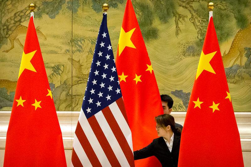 © Reuters. Помощники поправляют флаги перед открытием торговых переговоров США и Китая в Пекине