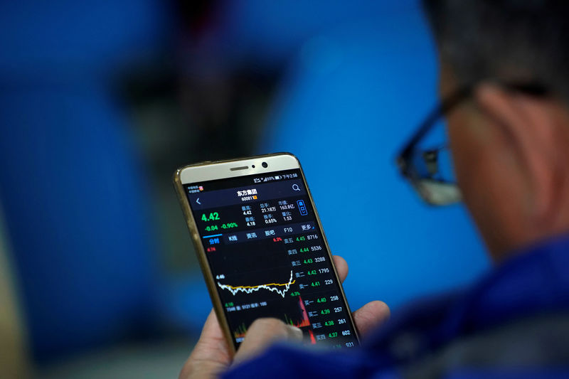 © Reuters. An investor checks stock information on a mobile phone at a brokerage house in Shanghai
