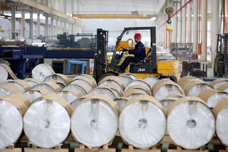 ©路透社。 工人在安徽淮北的一家工厂驾驶叉车经过铝卷
