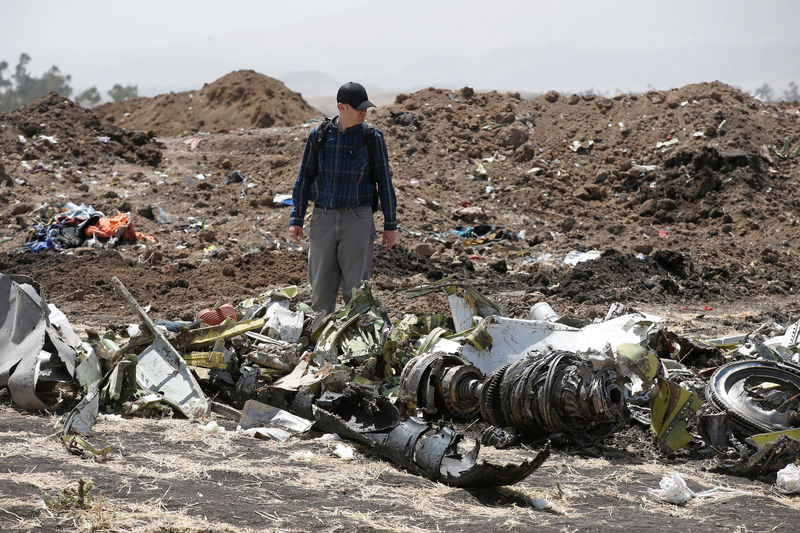 © Reuters. FILE PHOTO: American civil aviation and Boeing investigators search through the debris at the scene of the Ethiopian Airlines Flight ET 302 plane crash, near the town of Bishoftu, southeast of Addis Ababa