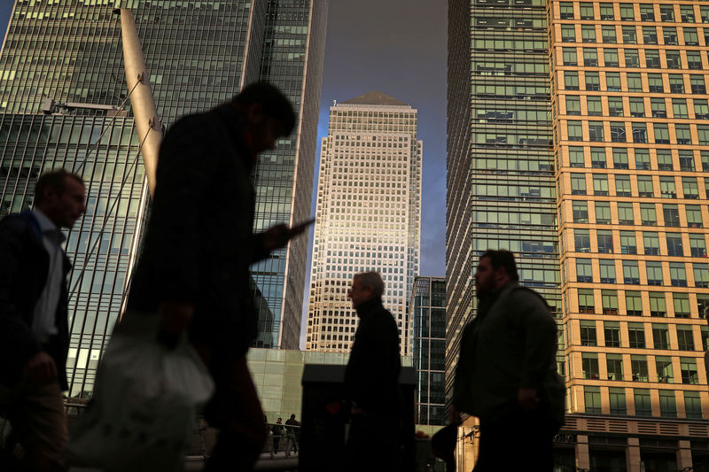 © Reuters. FILE PHOTO: People walk through the Canary Wharf financial district of London
