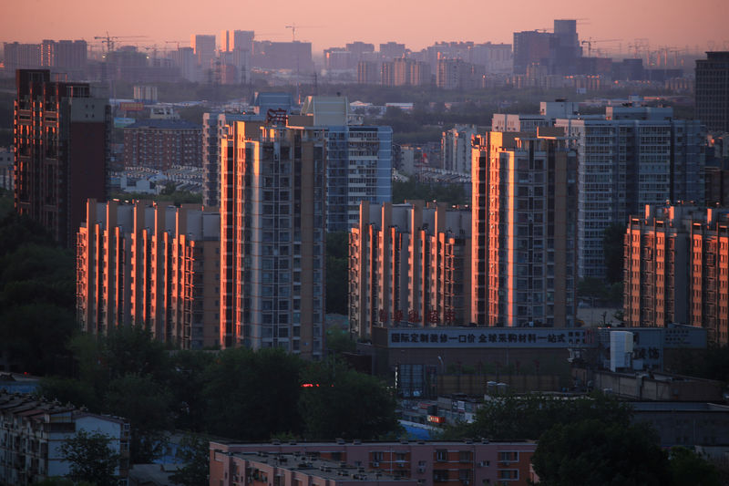 © Reuters. FILE PHOTO: Property buildings are seen against the dawn sky in Beijing