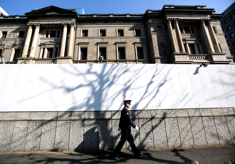 © Reuters. FILE PHOTO: A security guard walks past in front of the Bank of Japan headquarters in Tokyo