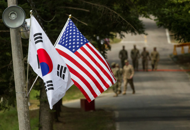 © Reuters. American and South Korean flags at Yongin South Korea