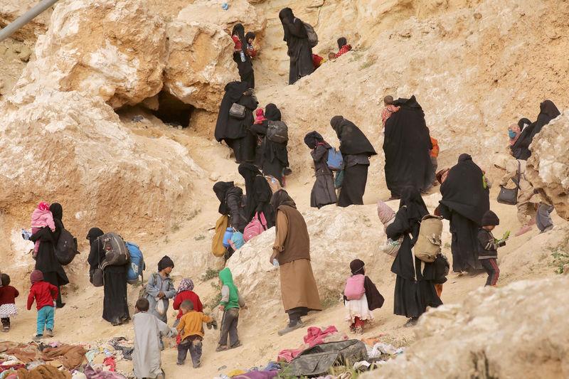 © Reuters. Familiares de militantes do Estado Islâmico que se renderam na vila de Baghouz, na Síria