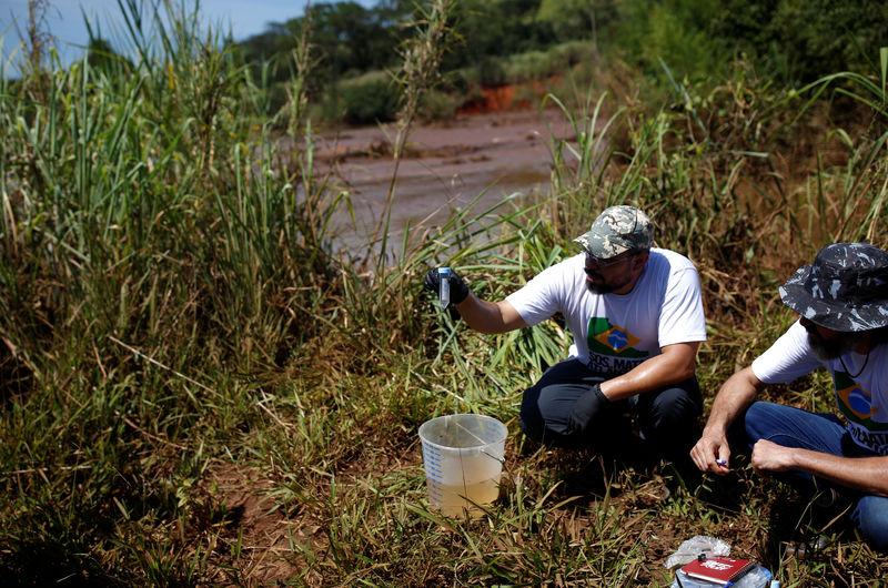 © Reuters. Membros do SOS Mata Atlântica coletam amostra de água do rio Paraopeba após desastre em Brumadinho (MG)