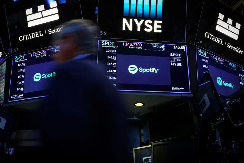 © Reuters. Merchant passes screens showing Spotify on NYSE floor in New York