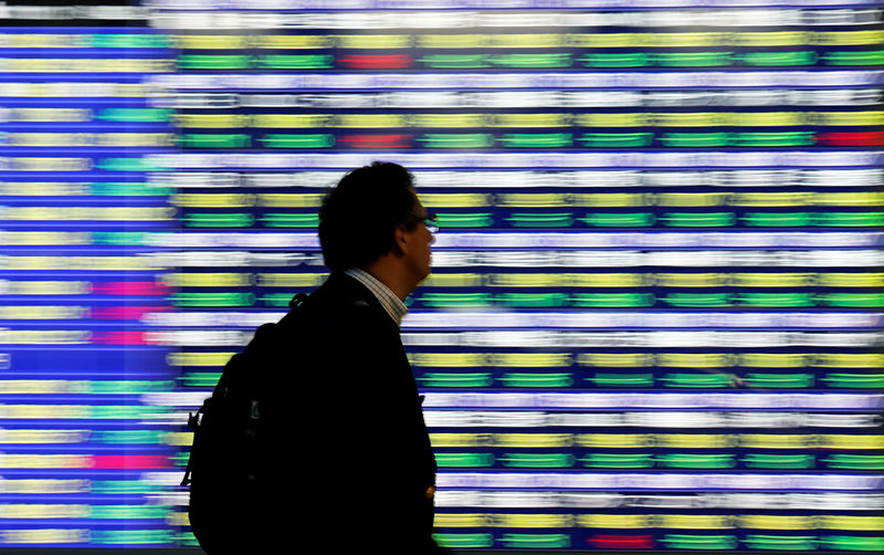 © Reuters. A man goes through an electronic stock quotation card outside of mediation in Tokyo