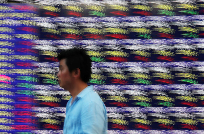 © Reuters. FILE PHOTO:  Passersby walk past in front of an electronic stock quotation board outside a brokerage in Tokyo